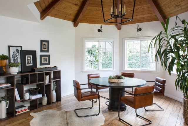 Dining room with black table, leather coated chairs, and black shelfs with books and pictures