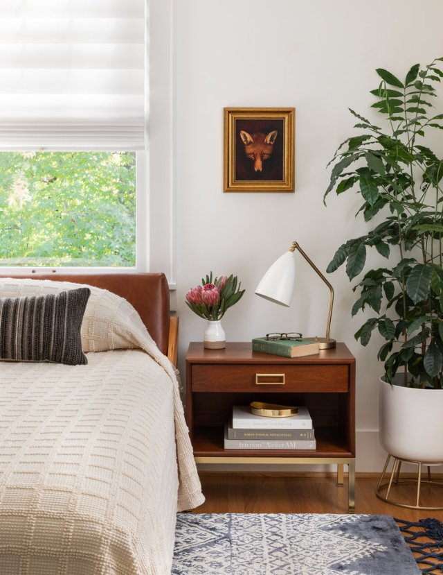 Bedroom with bed, picture and night stand with light, flowers in vase and books
