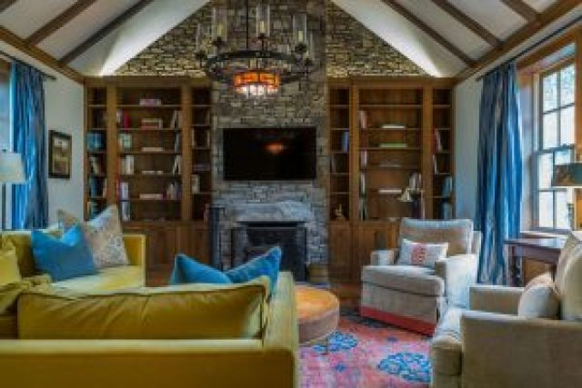 Cozy living room with green couch, rug, chairs, bookshelf and chandelier