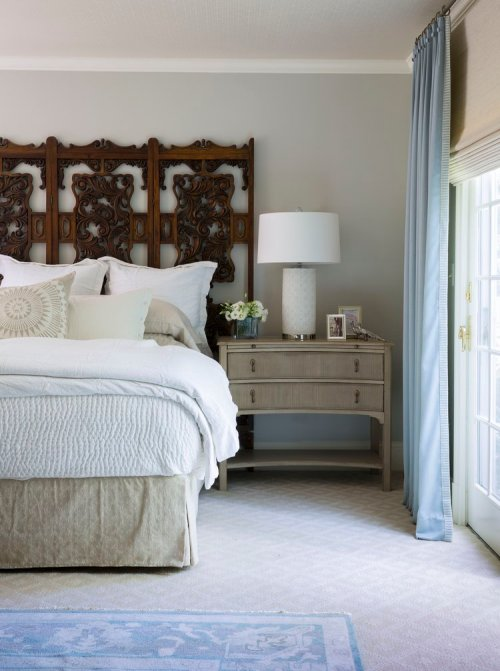 Bedroom with nightstand with lamp on top and curtains on the window