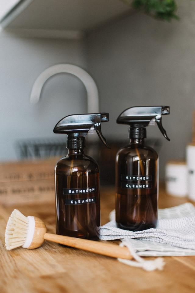 Labeled cleaning bottles with pump with brush on the kitchen stand