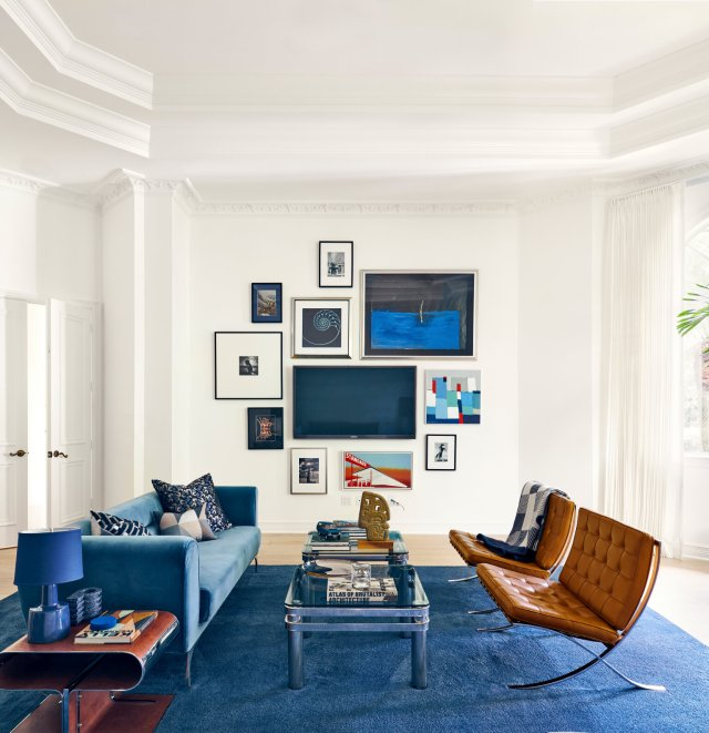 Blue and white living room with sofa, table, chairs and TV on the wall in the background