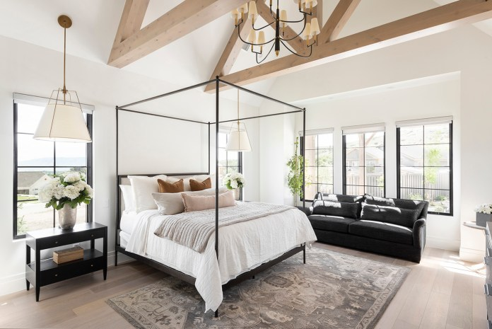 Bedroom with large framed bed, carped and wooden beams