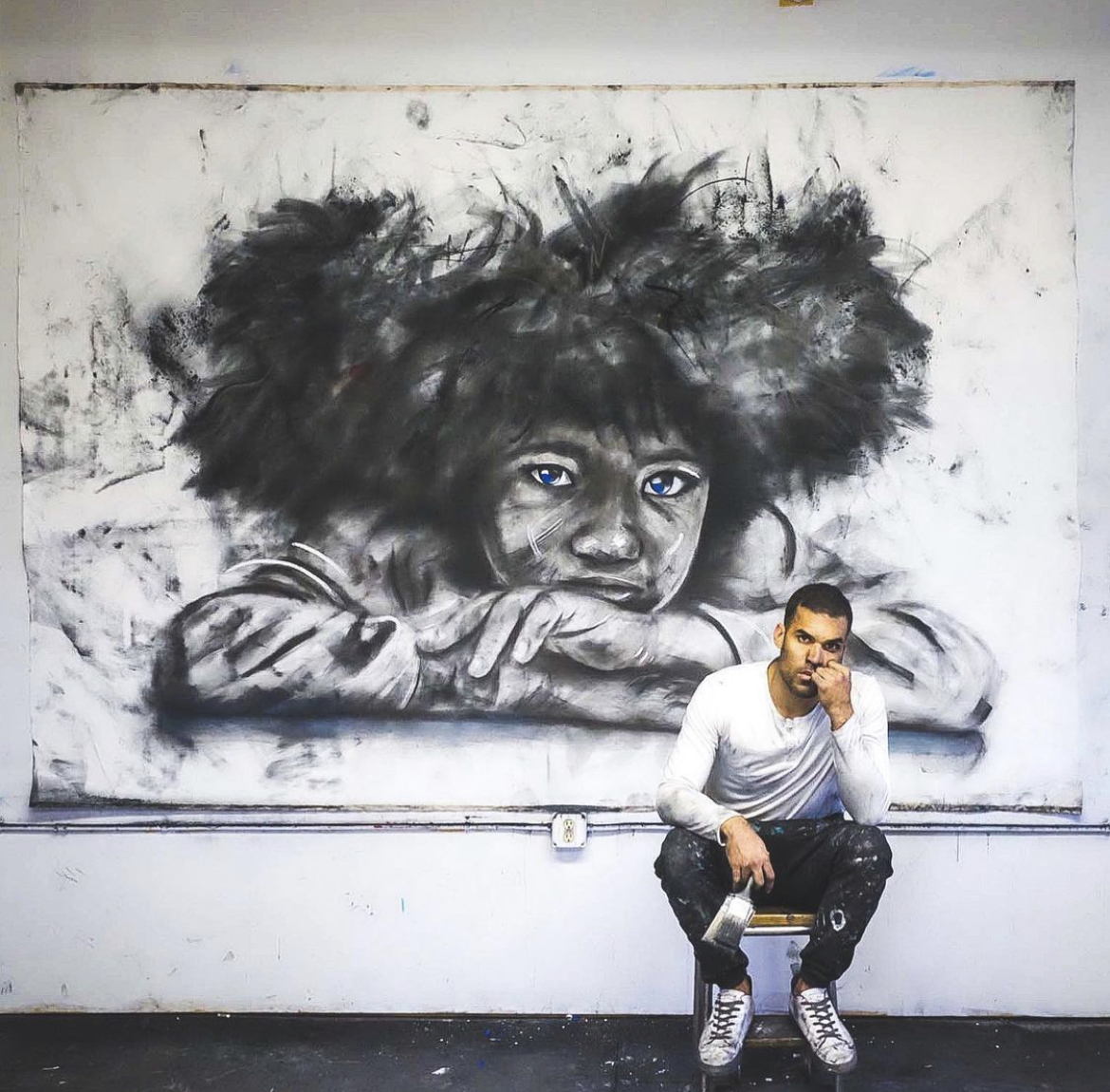 Artist Micah Johnson pictured in front of one of his works.