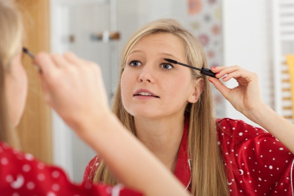 Blonde applying mascara