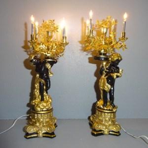 Each torchere figure holds a 3-arm chandelier
