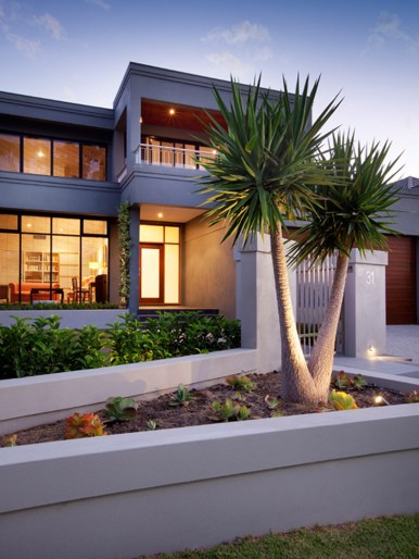 The front of a modern, minimalistic house with a huge two trunk Yuka plant in the front planter box