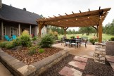 Overview of dining area underneath pergola with locally harvested chocolate flagstone stepping stones