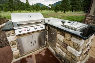 Outdoor kitchen was constructed with stone veneer to match the home and custom granite countertops. The outdoor kitchen consists of built in BBQ, drop in cooler, BBQ light, access doors, and double drawers