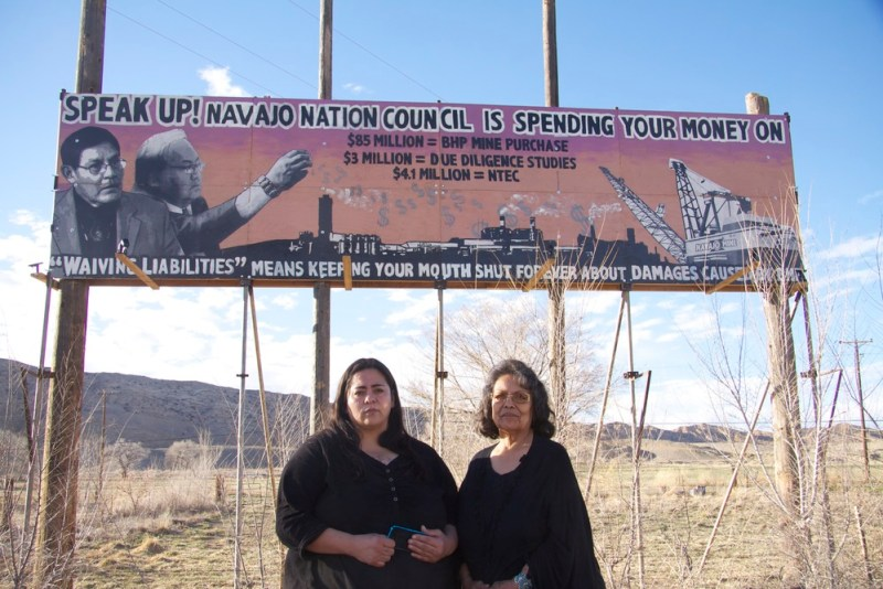 Victoria Gutierrez (left) and Sarah Jane White in front of the billboard they erected in protest against unfettered oil and gas development on Navajo lands. (Photo: Bobby Magill, www.climatecentral.org)
