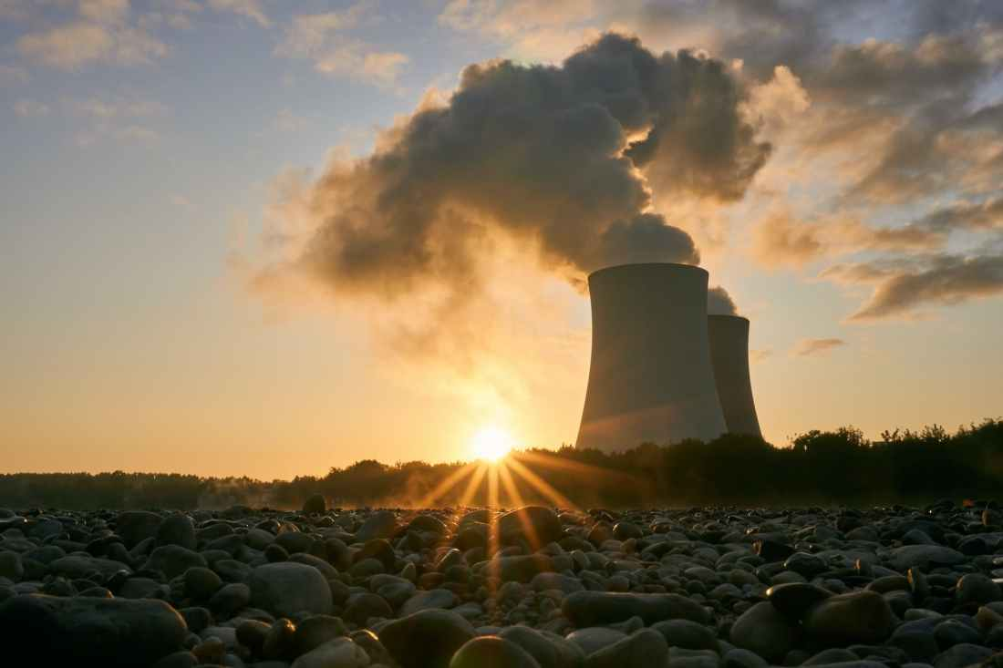 low angle photo of nuclear power plant buildings emtting smoke