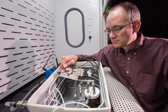 Sandia National Laboratories researcher Chris Brotherton checks tiny sensors in a test fixture, where he exposes them to different environments and measures their response to see how they perform. Brotherton is principal investigator on a project aimed at detecting a common type of homemade explosive made with hydrogen peroxide. (Photo by Randy Montoya)