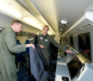 Lt. Cmdr. Colette Lazenka, Tactical Coordinator with Patrol Squadron (VP) 30, shows Chief of Naval Air Training Rear Adm. Mark Leavitt some of the new features of the P-8A Poseidon.(Photo: U.S. Navy  by Richard Stewart)