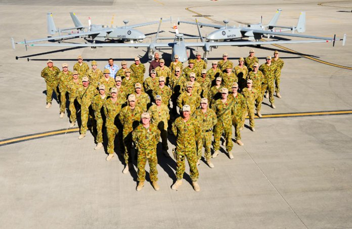 In November 2013 the Royal Australian Air Force Air Component completed 20,000 combat flying hours in Afghanistan. In this photo, the unit commanderGroup Captain Tony McCormack stands alongside members of theHeronRemotely Piloted Aircraft Detachment (Rotation 13) that operated the mission on this milestone flight. EachHerondetachment consists of about 30 ADF personnel based at Kandahar Airfield in Southern Afghanistan. Photo: RAAFChris Moore