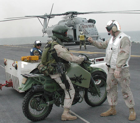 A member of the 15th Marine Expeditionary Unit (MEU) Special Operations Capable (SOC) waits his turn to onload his motorcycle for a helicopter flight into Kuwait. Photo: US Navy