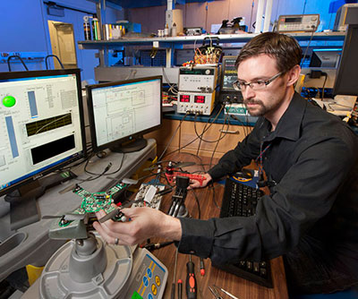 Dr. Joseph Conroy checks the vehicle operation of the ARL micro-quadrotor, a platform for testing integrated sensing and processing on size constrained robotic systems. (ARL Photo by Doug Lafon)