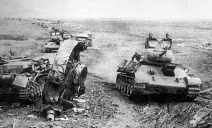 Russian T-34 column pass a destroyed German Pz-IV near Khrakov.