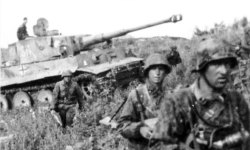 German soldiers of SS-Panzer Grenadier Division 'Das Reich' advance through the southern Voronezh Front during Battle of Kursk, covered by Panzer VI Tiger I tank. Photo: Bundesarchive
