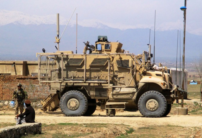 A MaxxPro MRAP sets up a secure position, allowing Soldiers from White Platoon, Apache Troop to dismount and conduct nearby street-level engagements with local villagers April 4, 2014. photo: U.S. Army by Joseph Krebsbach