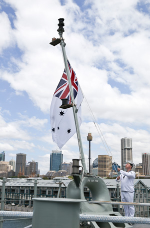 The Australian White Ensign raised onboard HMAS Canberra during the commissioning ceremony, Fleet Base East, Sydney. Photo: RAN by Helen Frank