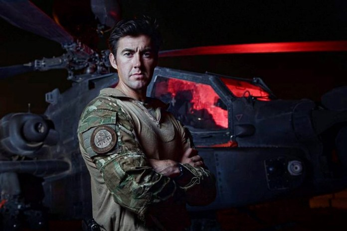 Portrait of an Apache pilot, standing in front of his Apache attack helicopter, prior to a mission in Helmand, Afghanistan in 2013. Photo: MOD, Crown Copyright by Corp. Si Longworth.