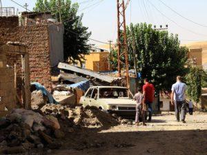 أشخاص يتنقلون عبر الأنقاض في أحد شوارع منطقة سيلفان في ديار بكر عقب اندلاع اشتباكات بين الجيش التركي والمتمردين الأكراد في 19 أغسطس. (صورة: AFP عبر غيتي إيمدجز)