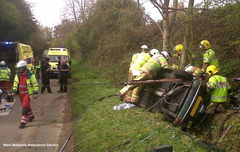 Road Safety West Midlands ambulance & fire service personnel in yellow hi viz inspecting an over turned car on a grass verge