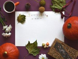 Une todo list sur une table où se trouve des feuilles mortes, un carnet, une tasse de café, des potirons...
