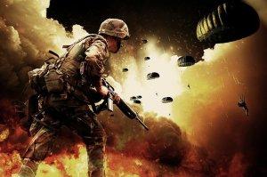 Un militaire au sol en premier plan, les autres descendent en parachutes.