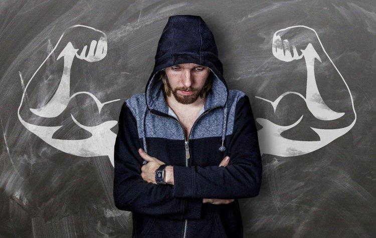 Un homme devant un tableau où est dessiné des bras musclés. Un rien peut tout changer.