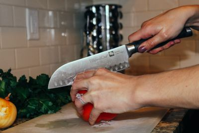 cutting bell pepper with chef's knife on white cutting board