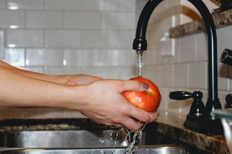 washing apple in sink