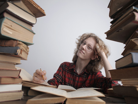 Woman in mid of stack of books
