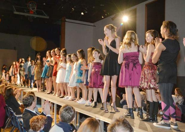 """Students who participated in """"Fashion for Change"""" pose on the runway."""