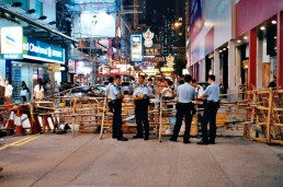 Police standing next to the barricade in Mong Kok, Kowloon.
