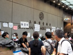 """A supplies station set up outside a Bank. With lots of posters saying """"To protect our safety, please do not photograph us"""" """"Peaceful Demonstration, Do Not Charge"""""""
