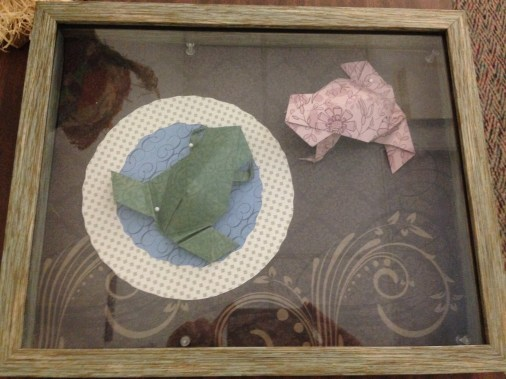 Two origami frogs, one is situated in the middle of a circular piece of paper.