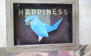 Origami bird sits in a small shadow box. small letters above it spell out happiness