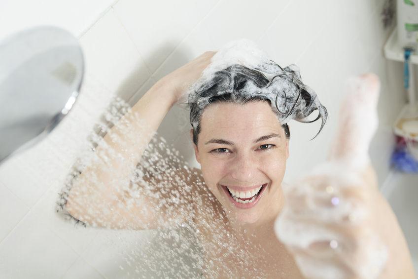 Frau beim Duschen und Heizöl sparen
