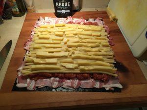 Bacon-Netz mit Hackfleisch und Makkaronis mit Käse belegt