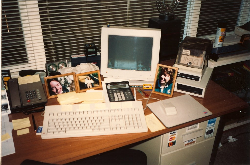 Desk with old Mac and photos