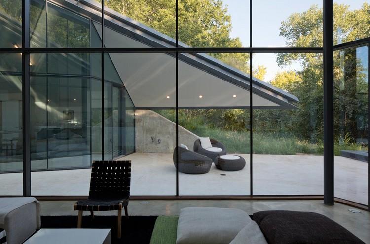Dinding kaca pembatas ruang keluarga dengan halaman belakang