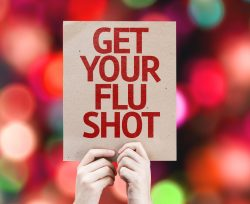 """person holding a sign that says """"get your flu shot"""""""