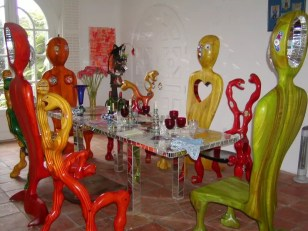 """These are some of the snake chairs and bird chairs that were built for Niki and are shown around her dinning room table. The Bird chairs are built up in what is called stacked lamination. They have mortise and tendon joints where the """"stacks"""" change direction (at the legs, tail and seat and body). The snake chairs are laminated and glued using epoxy and 1/4"""" thick wood sections. They are bent over a huge jig using over 150 champs to get the wood to go where it needed to. Both chairs are dyed for color, finished and have glass, jewels and Italian millaflore medallions inserted in mastic to allow for expansion."""