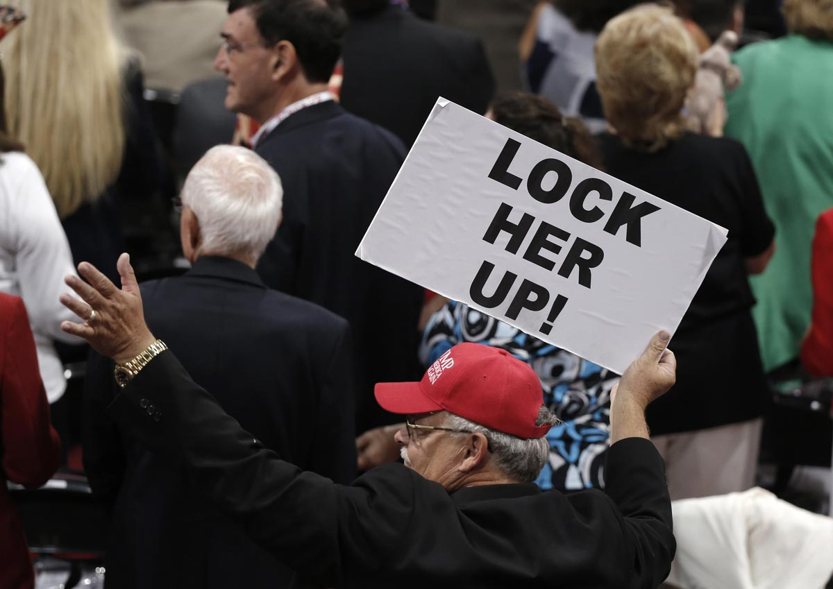 Delegate at the Republican National Convention holds sign, referring to Hillary Clinton | source: Mike Segar/Reuters
