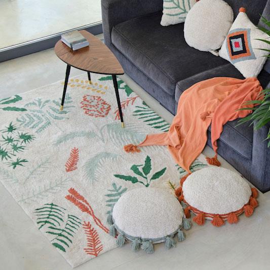 Alfombra lavable Botanical de Lorena Canals. Con estampado de hojas en distintos colores y fondo claro.