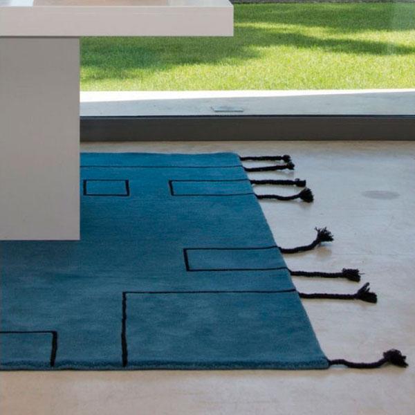 Alfombra de lana azul Nordic Lines de Lorena Canals colocada en un comedor
