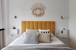 Proyecto de decoración de dormitorio en Madrid Río con cabecero amarillo y espejo de mimbre con forma de ojo, por Deleite Design