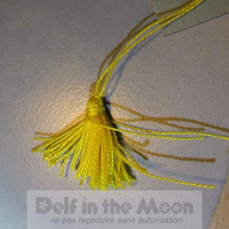 entourer le haut du pompon avec l'autre petit fil, plusieurs tours et faire un double noeud très serré.