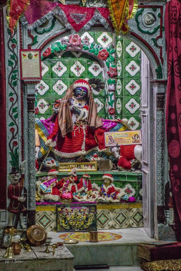 An idol of Lord Krishna dressed in Christmas clothing